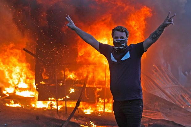 Carnage: A protester gestures as a riot police vehicle burns behind him during clashes in central Baghdad. Photo: Getty