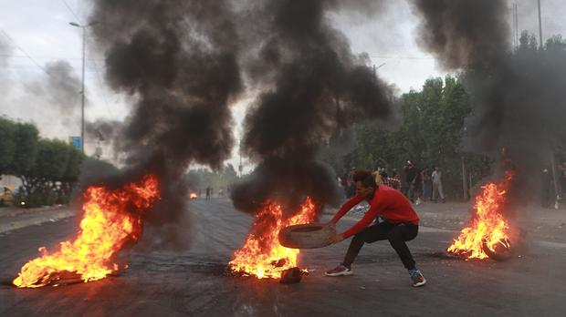 Anti-government protesters set fires and close a street during a demonstration in Baghdad (AP)