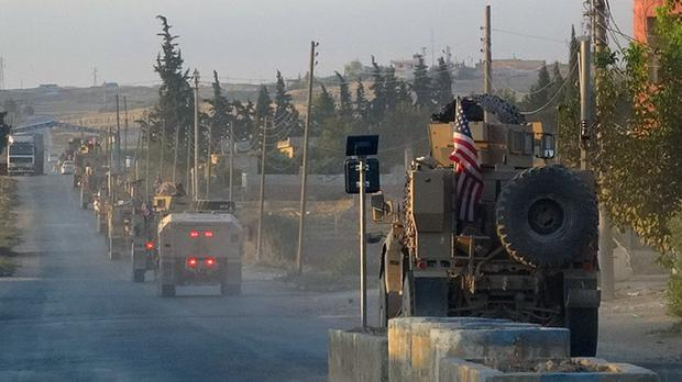 US military vehicles travel down a main road in north east Syria (ANHA via AP)