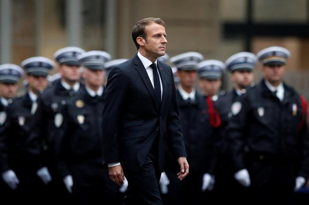 Homage: French President Macron at tribute to dead at Paris police HQ. Photo: REUTERS