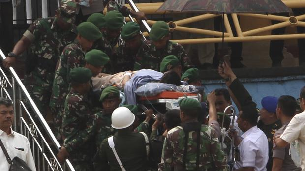 Soldiers carry Indonesian security minister Wiranto on a stretcher to a waiting helicopter after being stabbed (Rafsanjani/AP)