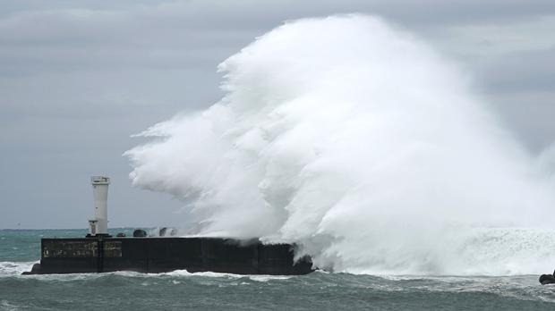 Surging waves caused by the approaching storm hit a breakwater in Mie prefecture, central Japan (Toru Hanai/AP)