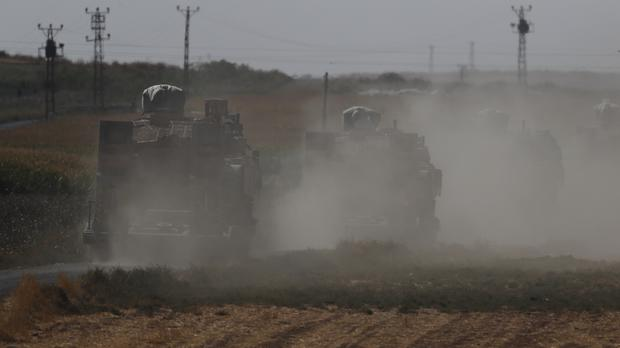 A convoy of Turkish forces' trucks transporting tanks is driven towards the border with Syria (Lefteris Pitarakis/AP)
