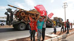 Military action: Boys wave Turkish flags as a convoy drives near the border town of Akcakale, Turkey. Photo: REUTERS/Kemal Aslan