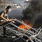An anti-government protester adds debris to block a highway that links to north Lebanon in east Beirut, Lebanon (Hussein Malla/AP)