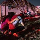 Henry Ramirez and his mother Maribel Morales survey damage to a church (Jeffrey McWhorter/AP/PA)