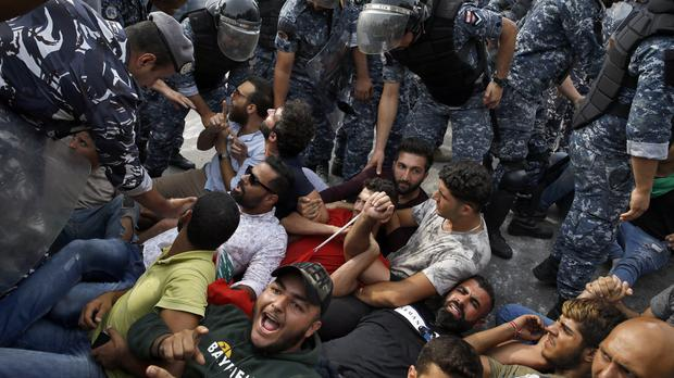 Police negotiate with anti-government protesters to unblock a main road in Beirut (Bilal Hussein/AP)