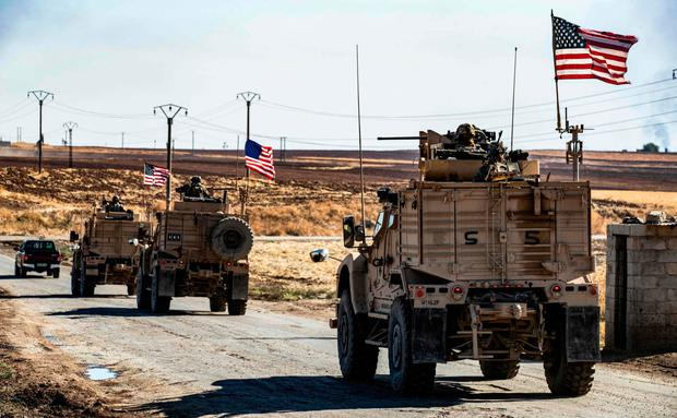 Mission: US military vehicles drive in a patrol past an oil well in Rumaylan, northern Syria, yesterday. Photo: Delil Souleiman/AFP