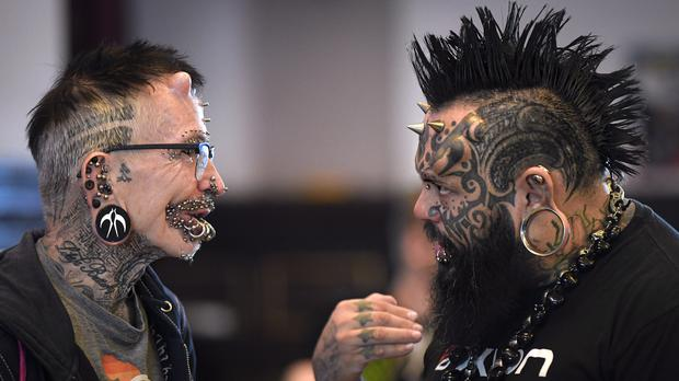 Guinness World Record holder Rolf Buchholz, left, known for his 453 metal piercings, speaks to Venezuela's Emilio Gonzales during the 10th International Tattoo Convention in Bucharest (Vadim Ghirda/AP)