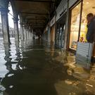 A shopkeeper looks out of his shop at a flooded St. Mark's Square on the occasion of a high tide, in Venice, Italy, Tuesday, Nov. 12, 2019. The high tide reached a peak of 127cm (4.1ft) at 10:35am while an even higher level of 140cm(4.6ft) was predicted for later Tuesday evening. (Andrea Merola/ANSA via AP)