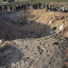 A barefoot Palestinian boy and others look into a crater made in overnight Israeli missile strikes that destroyed a house and killed eight members of the Abu Malhous family, in Deir al-Balah, central Gaza Strip (Khalil Hamra/AP)