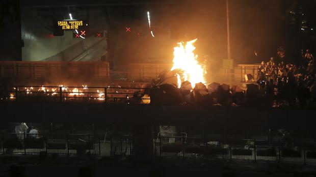 A fire burns at barricades built by protestors near the entrance to the Cross Harbour Tunnel in Hong Kong, Sunday, Nov. 17, 2019. A Hong Kong police officer was hit in the leg by an arrow Sunday as authorities used tear gas and water cannons to try to drive back protesters occupying a university campus and surrounding streets (Kin Cheung/AP)