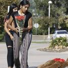 Saugus High School students Liliana, 15, right and her sister Alexandra, 16 bring a bouquet of roses for the Saugus High School victims at the Central Park in Santa Clarita (Damian Dovarganes/AP)