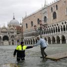 A city worker helps a woman who decided to cross St Mark's Square (Luca Bruno/AP)