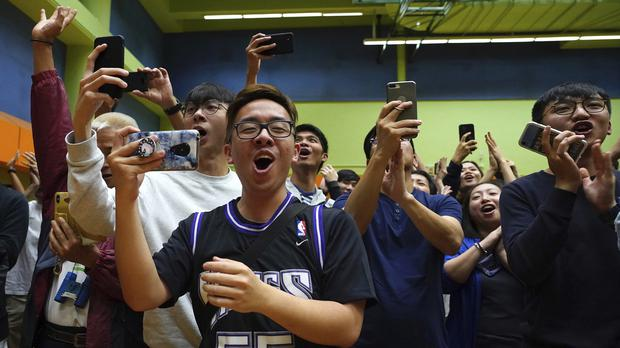Supporters of pro-democracy candidate Angus Wong celebrate after he won in district council elections (Vincent Yu/AP)