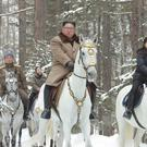 Kim Jong Un, centre, with his wife Ri Sol Ju, right, riding on white horse during his visit to Mount Paektu (Korean Central News Agency/Korea News Service/AP)
