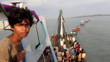 A fishing boat carrying Rohingya and Bangleshi migrants is pulled to shore by Achenese fisherman off the coast of Julok, in Aceh province May 20, 2015 in this photo taken by Antara Foto. Hundreds of Rohingya and Bangladeshi migrants landed in Indonesia's northwestern Aceh province early on Wednesday, an Indonesian search and rescue official said. REUTERS