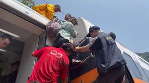 Rescue teams help stranded passengers down from the roof of the train. Photo: FACEBOOK @HUALIENFASTNEWS