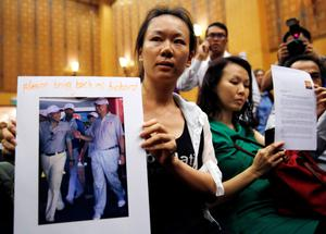 The wife of a passenger aboard the missing Malaysia Airlines Flight MH370, holds a picture of her husband