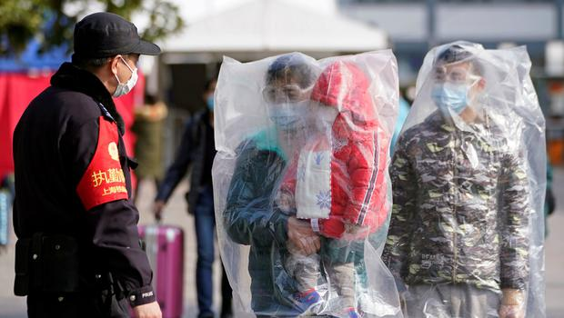 Cautious: Railway passengers in Shanghai wear full plastic bags in a bid to protect themselves from coronavirus. Photo: Aly Song/Reuters
