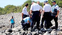 Police officers inspect metallic debris found on a beach in Saint-Denis on the French Reunion Island