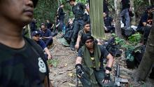 Policemen rest after hiking to the abandoned human trafficking camp in the jungle close the Thailand border at Bukit Wang Burma in northern Malaysia yesterday.