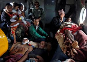 Victims of the earthquake rest inside an Indian Air Force helicopter as they are evacuated from Trishuli Bazar to the airport in Kathmandu, Nepal. Photo: Reuters