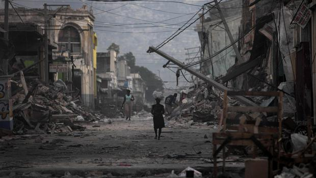A woman walks down a devastated street in Port-au-Prince after the quake in 2010.,