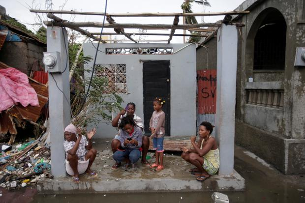 Women sit at the entrance of a house damaged by Hurricane Matthew in Les Cayes, Haiti Photo: AP/ Dieu Nalio Chery