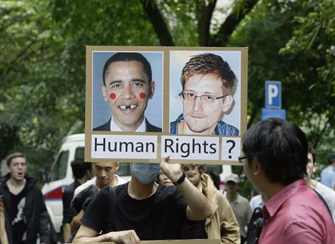 A man holds up a protest sign during the protest rally to support Edward Snowden in Hong Kong