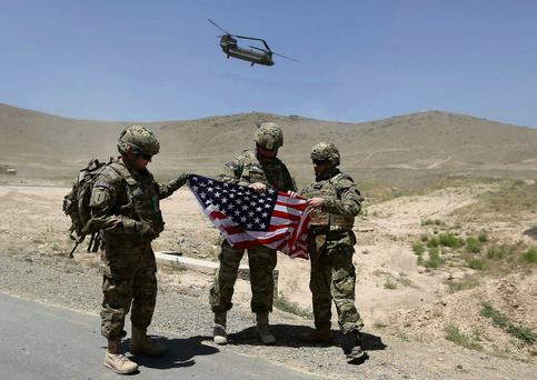NATO soldiers with a US flag as a Chinook helicopter takes off after a security handover ceremony at a military academy outside Kabul
