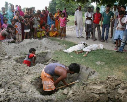 Villagers in the Indian state of Bihar dig graves to bury the 23 pupils who died after eating contaminated meals they were given at school