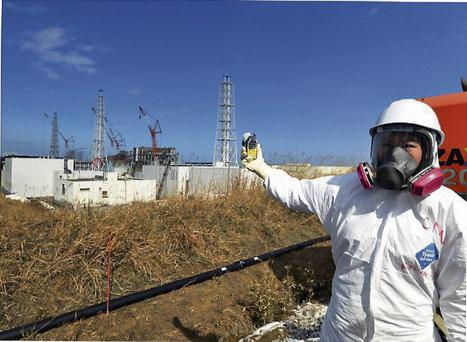 A journalist checks radiation levels with her dosimeter near the crippled TEPCO's Fukushima Daiichi nuclear power plant reactor buildings in Fukushima