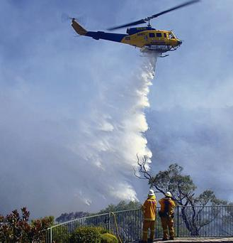Firefighters watch as a helicopter drops water on a fire approaching homes near the Blue Mountains suburb of Faulconbridge, around 80km west of Sydney, yesterday.