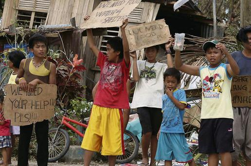 Children hold signs asking for help and food along the highway in Tacloban city