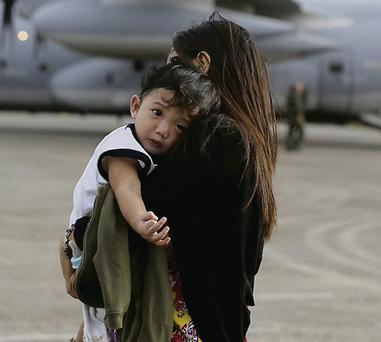 A mother carries her child at Manila's military airport, having arrived from Tacloban. REUTERS