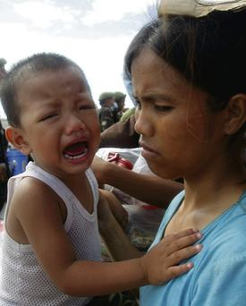 A mother and her distraught son wait at Tacloban airport for a plane to airlift them to the capital
