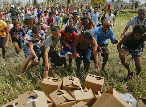 Survivors rush to grab fresh water delivered by a US helicopter.