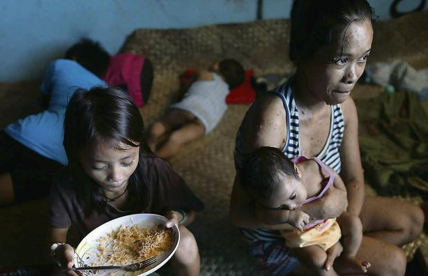 A family shelters in the ruins of Tacloban Stadium