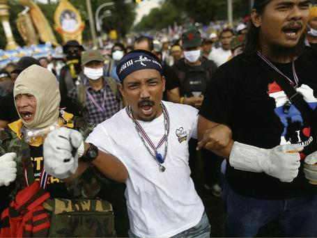 Anti-government protesters link arms and shout as they get ready to attack a police barricade near the Government house in Bangkok