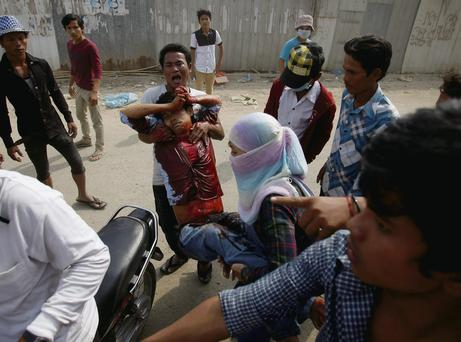 An injured garment worker is helped by colleagues.