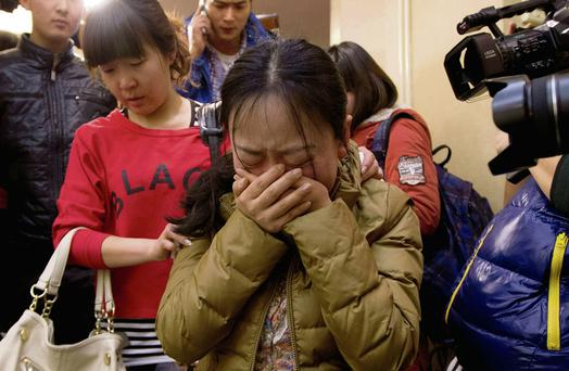 A Chinese relative of passengers aboard the missing plane, centre, cries as she waits for news.