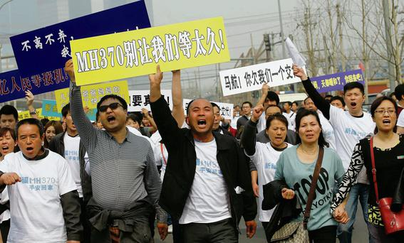 Families of the passengers on MH370 march on the Malaysian embassy in Beijing.