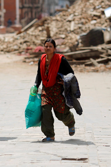 A woman rushes for safety during a strong aftershock