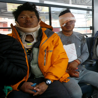 Injured Sherpa guides sit inside a bus after they were evacuated from Mount Everest Base Camp