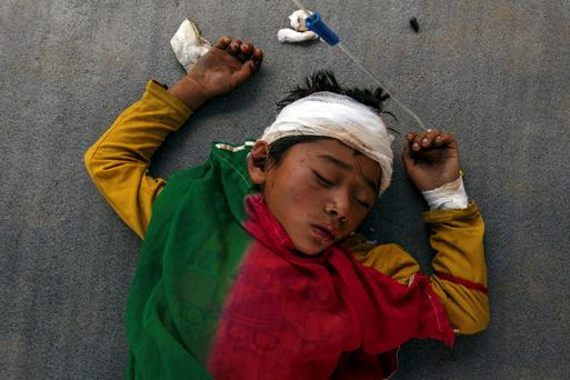 An injured boy sleeps on the ground outside the overcrowded Dhading hospital in Nepal. Photo: Reuters