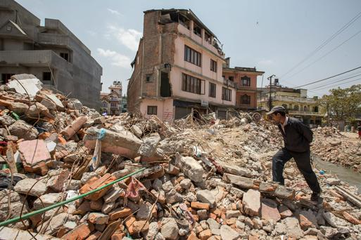 A man walks through rubble in Kathmandu, Nepal, inspecting an area devastated by the earthquake