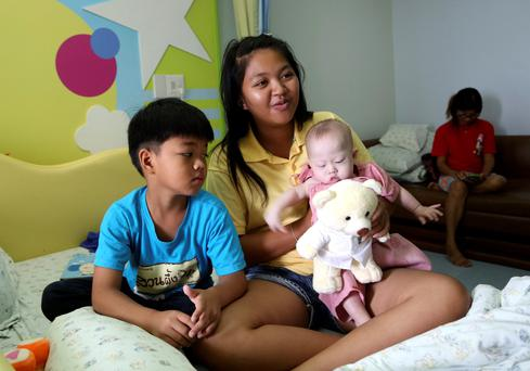 Pattaramon Chanbua with her children Game (7) left, and baby Gammy who was left in Thailand.