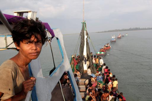 A fishing boat carrying migrants is pulled to shore by Achenese fisherman off the coast of Julok, in Aceh, Indonesia. Hundreds of Rohingya and Bangladeshi migrants landed in Indonesia's northwestern Aceh province early yesterday, an Indonesian search and rescue official said. Photo: Antara Foto/Reuters.