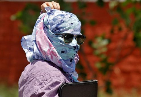 A woman walks along the road with her face covered to protect herself from sun stroke on a hot summer day in Chandigarh, India